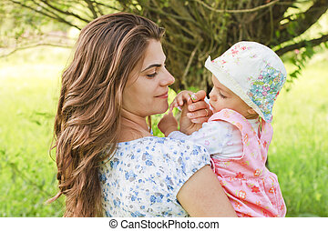 Baby girl with her mother giving a flower