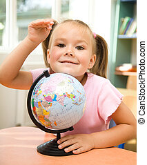 Little girl is playing with globe