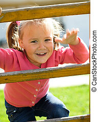 Cute little girl is climbing up on ladder