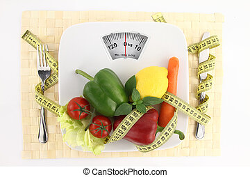 Diet concept - Vegetables with measuring tape on a plate as...