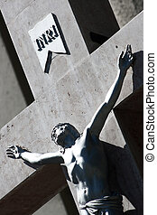 inri - Detail of Jesus on cross in front of church
