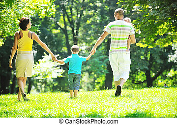 happy young couple with their children have fun at park -...