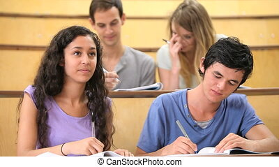 Students taking notes while their classmates are chatting in...