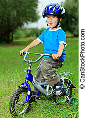 bicycling - Happy boy on a bicycle in a summer park.