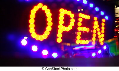 Glowing open neon display sign in a window, rack focus with...