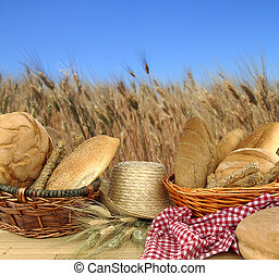 Various types of bread in front of a wheat field