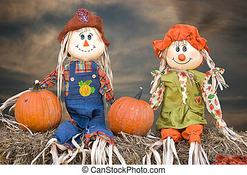 autumn scarecrow couple - Scarecrow couple sitting on hay...
