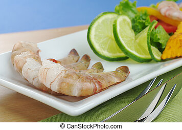 Raw king prawn with lime slices and lettuce on white plate,...