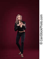 Beauty woman posing in sexy leather jacket on red