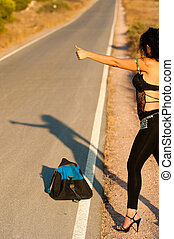 Sexy hitchhiker trying her luck on a lonely road