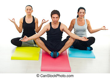 Three people doing yoga and sitting on colorful mats with...