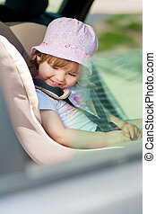little girl in safety seat - laughing little kind sitting in...