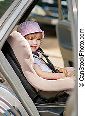 protected girl - little cute girl in cap sitting in the car...