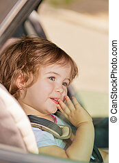 kid making faces sitting in car safety seat - little baby...