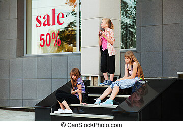 Teenage girls relaxing on a shop steps