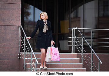 Young woman with shopping bags on the steps