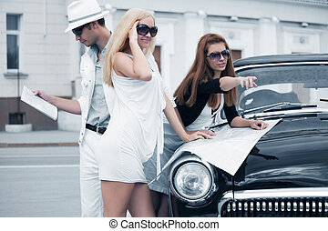 Young tourists with a road map on the retro car