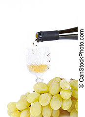 White wine pouring in the goblet and grapes isolated in white
