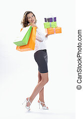 Woman holding shopping bags and gift box against a white...