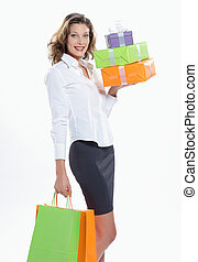 smiling Woman holding shopping bags and gift box against a...