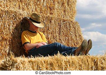 Sleepy Cowboy - Cowboy sitting on straw stack with feet...