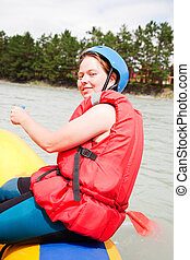 girl - sportswoman on a raft floats on the mountain river