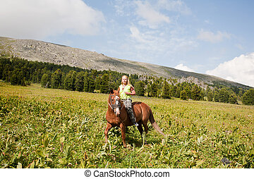 girl on a meadow astride a horse