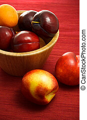 Juicy nectarines, plums and apricots on red background
