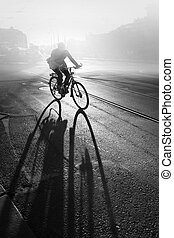 Cyclist - Silhouette of cyclist at sunrise, casting a long...