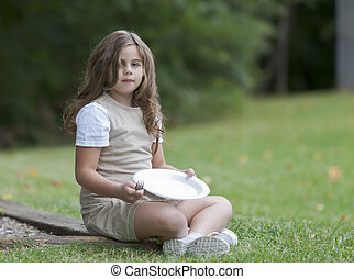 Hungry Child - Lonely child sitting in a park with an empty...