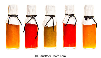 Hot Sauce - Five hot sauce bottles with white tops on a...