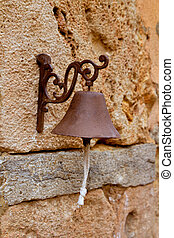 Aged rusty iron little bell hanging from stone wall in...