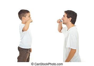 Father teaching his son to brushing teeth isolated on white...