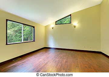 Large yellow empty room with large window and wood floor -...