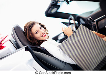 attractive woman in car with shopping bags