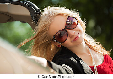 Happy young blond with a new convertible car