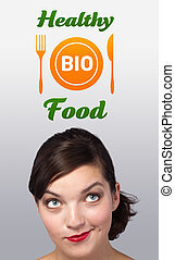 Young girl looking at healthy food sign