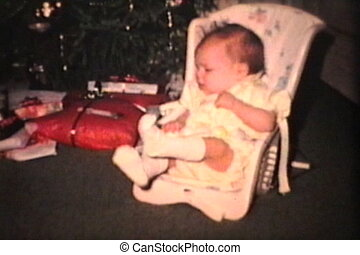 Baby Girl By Christmas Tree 1965 - A newborn baby girl sits...