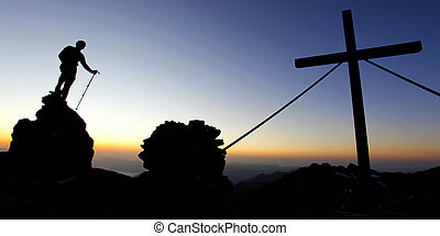 Silhouette of a man on a mountain summit at dawn