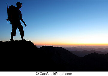 Silhouette of a man in the mountains at dawn