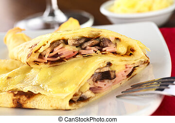 Rolled crepes filled with ham, cheese and white mushroom and...