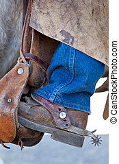 Boot with spur in the saddle - Close up of the booted foot...