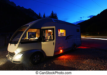 Camper van parked at night next to the road