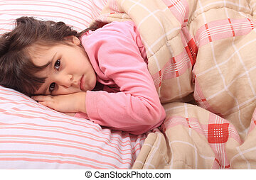 Little girl bedtime - Cute little girl laying in bed and...