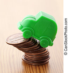 Green car miniature over pennies