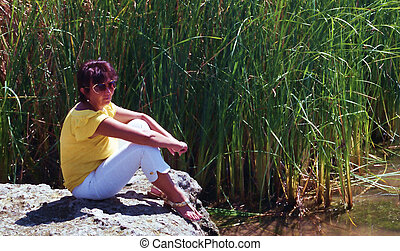 the Reeds - Young woman sitting on rock among the reeds -...