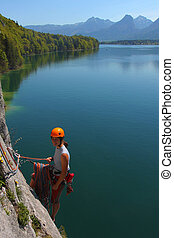 Young woman with climbing gear above alpine lake in Upper Austria