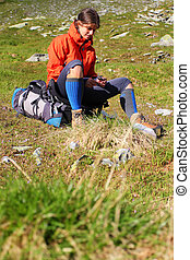 Young woman resting on her backpack during mountain hike
