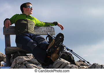 Young man hiker sitting on a bench enjoying the view