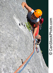 Summer climbing. Young woman climbing a limestone rock